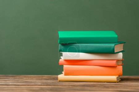 Photo for Stack of colorful books on wooden surface isolated on green - Royalty Free Image