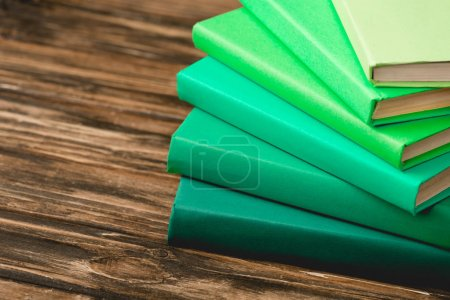 stack of colorful books on wooden textured surface