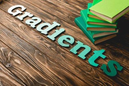 Foto de Libros verdes y letras sobre superficie texturizada de madera - Imagen libre de derechos