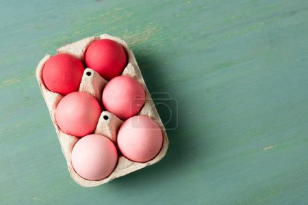 Photo for Top view of painted easter eggs in cardboard carrier on textured surface - Royalty Free Image