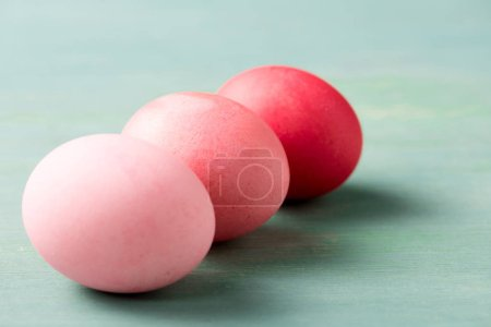 Photo for Painted pink easter eggs on blue textured surface - Royalty Free Image