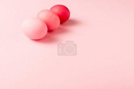 Photo pour Trois oeufs colorés peints de pâques sur la surface rose - image libre de droit