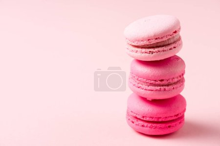 Photo for Three colorful tasty macarons with filling on pink - Royalty Free Image