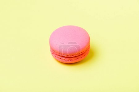 Photo for Pink macaron cookie with filling on yellow surface - Royalty Free Image