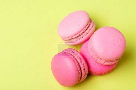 Photo for Tasty pink macarons with filling on yellow surface - Royalty Free Image