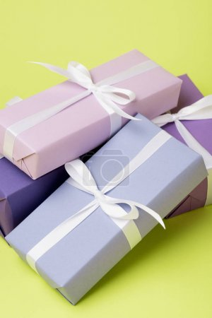 Photo for Purple gift boxes with white ribbons on yellow surface - Royalty Free Image