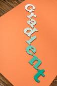 """Постер, картина, фотообои """"градиентное слово из зеленых букв на ярко-оранжевой бумаге"""""""