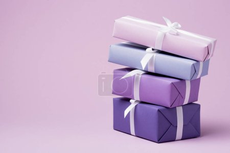 Photo for Colorful gift boxes with white ribbons on purple surface - Royalty Free Image
