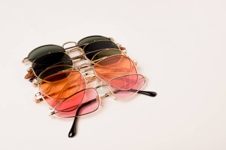 Photo for Stylish colorful sunglasses on white surface with copy space - Royalty Free Image