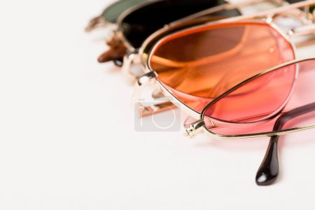 selective focus of stylish colorful sunglasses on white surface