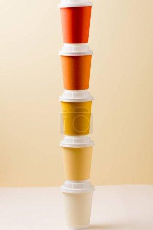 Photo pour Tasses jetables colorées sur la surface légère d'isolement sur le beige - image libre de droit