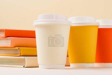 Photo pour Pile de livres et gobelets jetables colorés sur surface blanche isolé sur beige - image libre de droit
