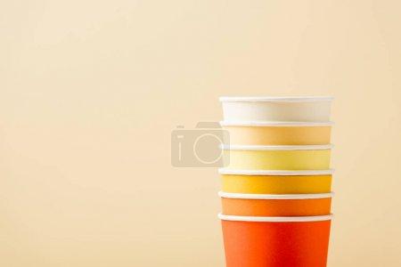 Photo pour Gobelets jetables colorés lumineux isolés sur fond beige - image libre de droit