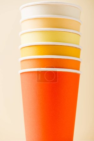 bright colorful disposable cups isolated on beige background