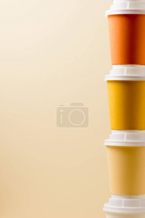 Photo for Colorful disposable cups with white caps isolated on beige - Royalty Free Image