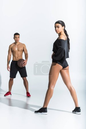 Photo pour Mixed race man with ball looking at attractive sportive african american girl on white - image libre de droit