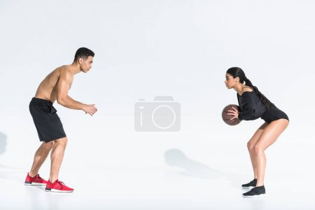 Photo pour Sportive multicultural young man and woman playing ball on white background - image libre de droit