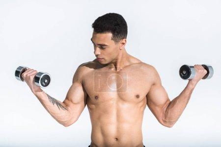 Photo pour Beau homme de course mixte athlétique avec le torse musculaire retenant des haltères sur le blanc - image libre de droit