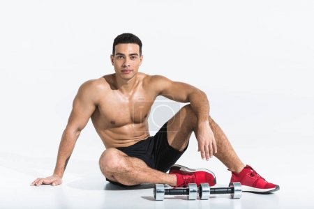 Photo for Handsome sportive mixed race man sitting on floor near dumbbells on white - Royalty Free Image