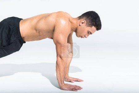 Photo pour Beau sportif homme de race mixte faire push ups sur blanc - image libre de droit