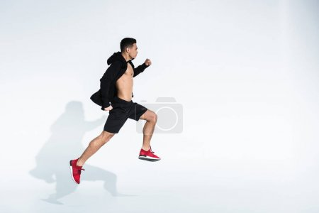 Photo for Side view of sportive mixed race man in black sportswear running on white - Royalty Free Image