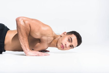 Photo for Handsome sportive mixed race man doing push ups and looking at camera on white - Royalty Free Image