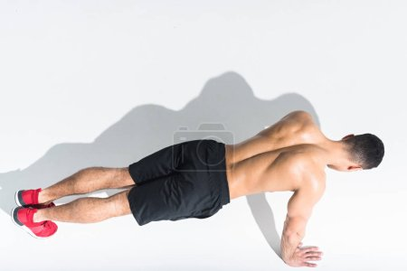 Photo for Overhead view of shirtless athletic man doing push ups on white - Royalty Free Image