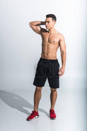 Photo pour Beau sportif homme de course mixte en short noir et baskets rouges sur blanc - image libre de droit