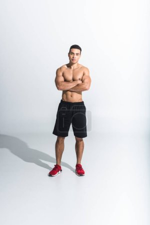 Photo for Handsome sportive mixed race man in black shorts and red sneakers looking at camera on white - Royalty Free Image