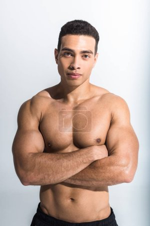 Photo for Handsome sportive mixed race man posing with crossed arms on white - Royalty Free Image