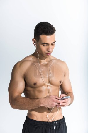 handsome sportive mixed race man in earphones holding smartphone and listening music on white