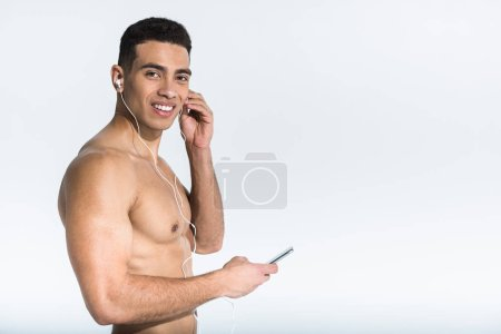Photo for Handsome athletic mixed race man listening music in earphones and looking at camera on white - Royalty Free Image