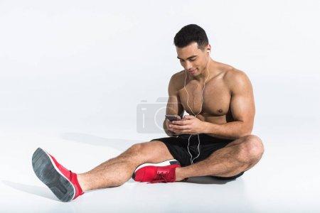 Foto de Guapo hombre de carreras mixta sportive sentado en el suelo y escuchar música en los auriculares en blanco - Imagen libre de derechos