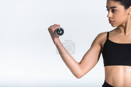 beautiful athletic african american girl training with dumbbell on white