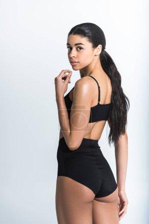 Photo pour Belle sportive fille américaine africaine dans le soutien-gorge noir de sports et les shorts regardant l'appareil-photo sur le blanc - image libre de droit