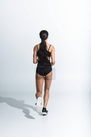 Photo for Back view of sportive african american girl running on white background - Royalty Free Image