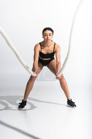 Photo for Beautiful sportive african american girl training with white ropes on white - Royalty Free Image