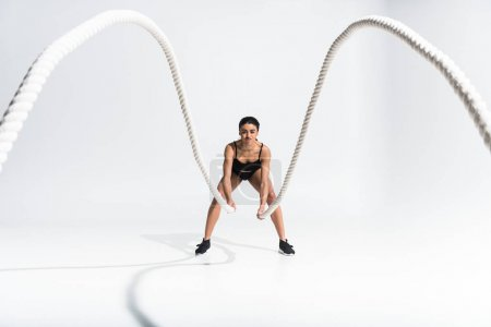 Photo for Selective focus of sportive aafrican american girl doing exercise with ropes on white - Royalty Free Image