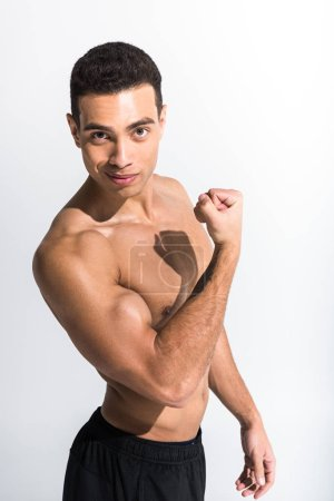 Photo for Handsome mixed race man demonstrating biceps and looking at camera on white - Royalty Free Image