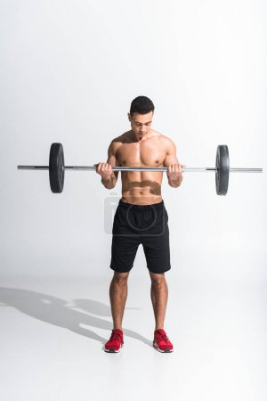 Photo for Athletic mixed race man in black shorts and red sneakers holding barbell on white - Royalty Free Image