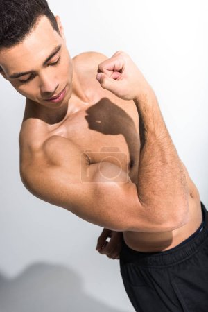 Photo for Handsome athletic mixed race man demonstrating biceps on white background - Royalty Free Image