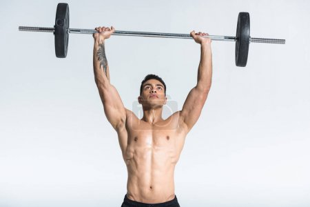 Photo for Handsome sportive mixed race man lifting barbell on white background - Royalty Free Image