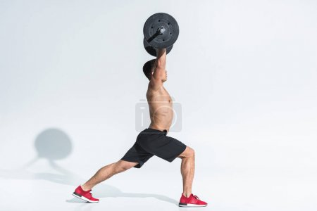Photo for Side view of athletic mixed race man in black shorts and red sneakers lifting barbell on white - Royalty Free Image