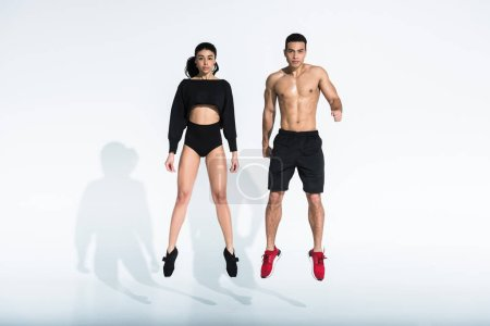 Photo pour Homme et femme multiculturels sportifs sautant sur le fond blanc - image libre de droit