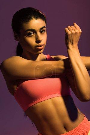 Photo pour Belle sportive africaine fille américaine se réchauffer et en regardant la caméra isolée sur violet - image libre de droit