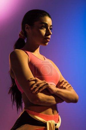 Photo pour Fille américaine africaine sportive dans le soutien-gorge rose de sports posant avec les mains croisées sur le fond pourpre et bleu de gradient - image libre de droit