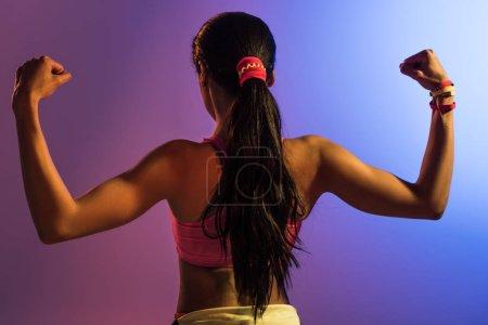 Foto de Vista posterior de la chica afroamericana atlética sobre fondo degradado púrpura y azul - Imagen libre de derechos
