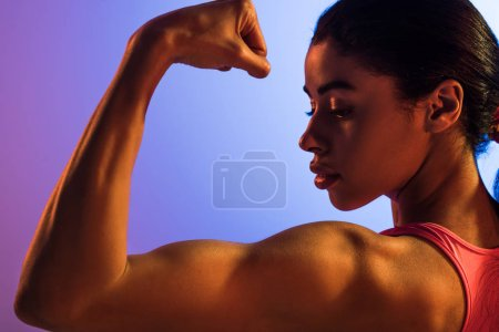 Photo for Beautiful athletic african american girl demonstrating biceps on purple and blue gradient background - Royalty Free Image