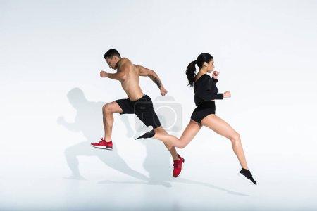 Photo pour Fille américaine africaine sportive et homme de course mélangé athlétique fonctionnant sur le fond blanc - image libre de droit