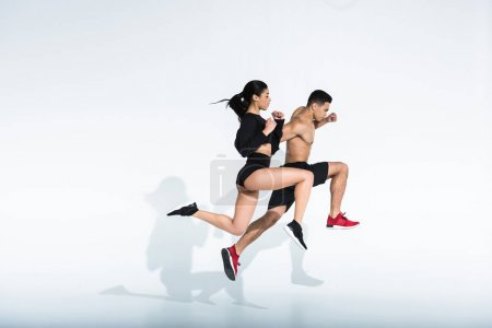 Photo for Side view of sportive multicultural woman and man in sportswear and sneaker running on white background - Royalty Free Image